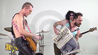 Zespół Punka Strzelanie do klipu Muzycy skakają z instrumentami Bass-player jest ubrany w damską sukienkę zbiory