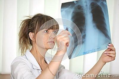 Ziekte. Vrouwelijke arts die een röntgenstraal onderzoekt
