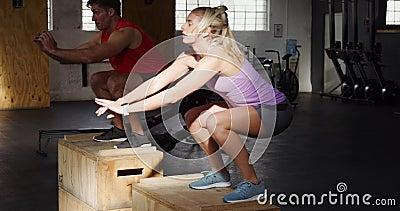 Zijaanzicht atletische blanke man en vrouw die op dozen springen stock videobeelden