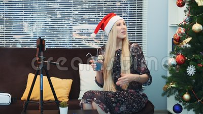 Zijaanzicht van gelukkige jonge dame in de opnamevideo van de Kerstmanhoed door smartphone op driepoot stock footage