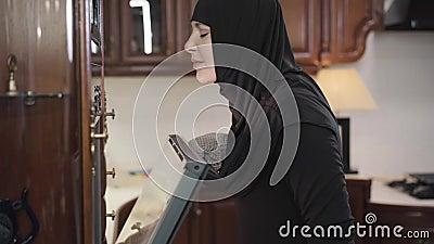 Zijaanzicht van jonge moslimvrouw in de zwarte hijab-openingsoven en het smelten van gebakken voedsel Tevreden oosterse dame in stock video