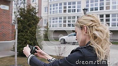 Zijportret die van een mooi blond meisje die een slimme telefoon met behulp van aan netwerk, selfies beelden in een huis nemen in stock videobeelden