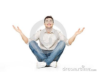 Zittende gelukkige mens met opgeheven omhoog handen