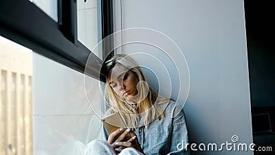 Zmartwiona kobieta używa telefon komórkowego blisko okno 4k zbiory