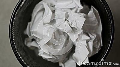 Zmięci papierów kawałki opuszczali w kubeł na śmieci zbiory
