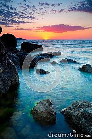 Zonsondergang over rotsachtige kustlijn