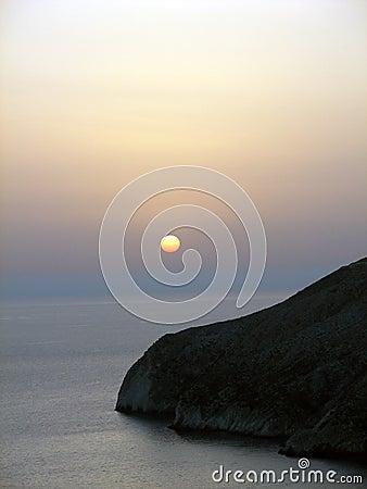 Zonsondergang. Rots in Ionische overzees