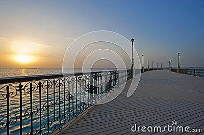 Zonsopgang over de oceaan bij een pijler