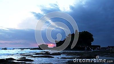 Zoom au coucher du soleil, photo du temple pura tanah lot sur l'île de bali banque de vidéos