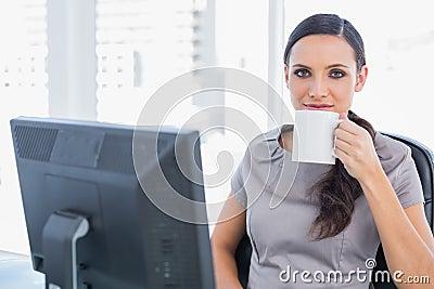 Zrelaksowany atrakcyjny bizneswoman pije herbaty