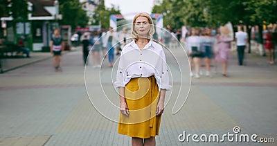 Zumbe para fora o lapso de tempo da mulher madura bonita que olha a posição da câmera na rua video estoque