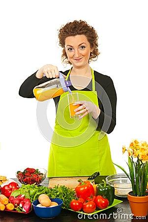 Zumo de naranja vertido mujer en vidrio