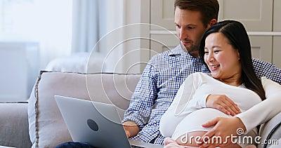 Zwanger paar die laptop op bed in woonkamer 4k met behulp van stock footage