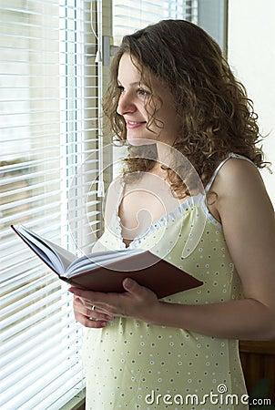 Zwangere vrouw dichtbij venster