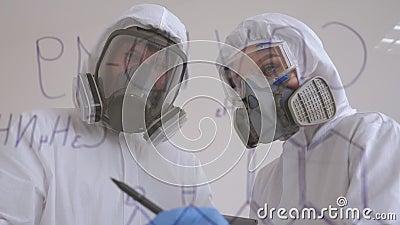 Zwei Ärzte in Schutzanzügen untersuchen das neue Covid-19-Virus im Labor stock video footage