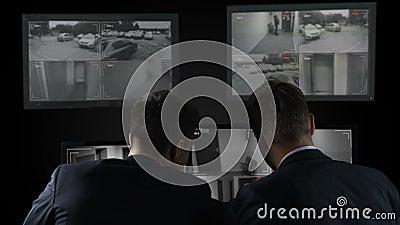 Zwei Detektive, die Überwachungskameraaufzeichnungen nach Verbrechen, Untersuchung überprüfen stock footage