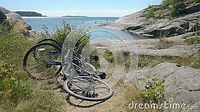 Zwei Fahrräder werden unter den Küstenfelsen auf dem Ufer der Nordsee vergessen stock video