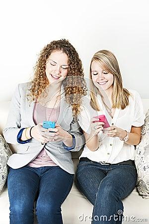 Zwei Frauen, die tragbare Geräte verwenden