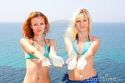 Zwei Frauen im Bikini, der zum Meer einlädt