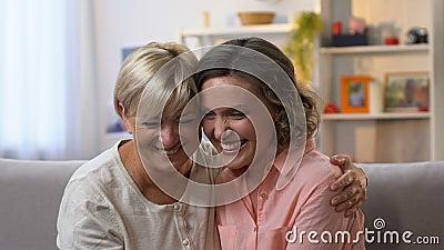 Zwei Freundinnen, die zusammen auf Couch, Klatschen lachen und Spaß, LangsammO haben stock video footage
