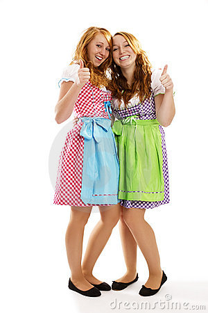 Zwei glückliche bayerische gekleidete Mädchen, die sich Daumen zeigen