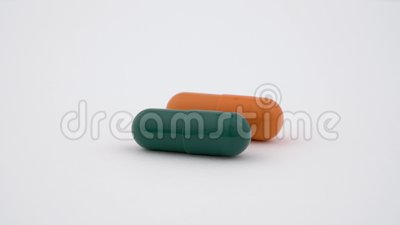 Zwei harte Stärkekapseln, die auf die Drehscheibe sich drehen Orange und grüne Farbe Getrennt auf weißem Hintergrund Abschluss ob stock video