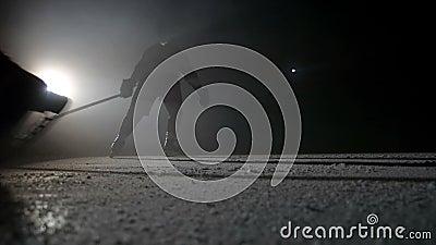 Zwei Hockeyspieler machen Eisscheine auf der hohen Geschwindigkeit, die in der Dunkelheit auf Arena bremst stock video footage