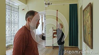 Zwei intelligente Männer im Museum schauen sich die Ausstellung an und sprechen über Kunst stock video footage