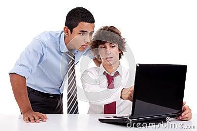 Zwei junge Geschäftsmänner, die zusammen an einem Laptop arbeiten