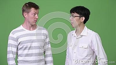Zwei junge multiethnische Geschäftsmänner verwechselt mit verschiedenen Entscheidungen stock video footage