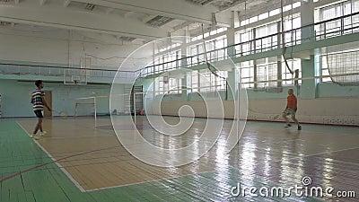 Zwei Kerl-Spiel-Badminton-in der Schule Sporthalle stock video