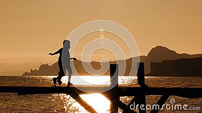 Zwei Kinder, die auf Brücke bei Sonnenuntergang laufen stock footage