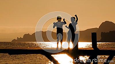 Zwei Kinder, die auf Brücke bei Sonnenuntergang tanzen stock video