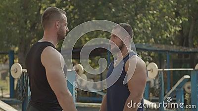 Zwei konkurrierende Bodybuilder stehen im Freien gegenüber stock video footage