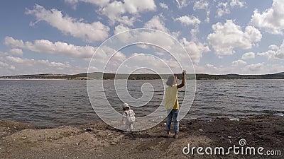 Zwei Mädchen werfen Steine in das Wasser Langsame Bewegung stock video