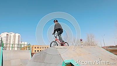 Zwei M?nner auf einem Fahrrad, das H?gel im skatepark hinuntergeht stock video footage