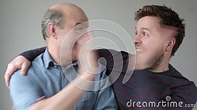 Zwei Männer Vater und Sohn fröhlich geben, hohe fünf, schauen sich gegenseitig, aufgeregt feiern einige Erfolg stock footage