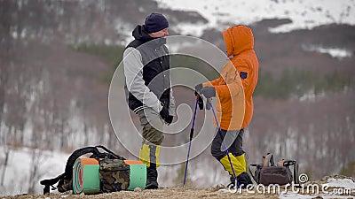 Zwei Mannhalt auf die Oberseite des Hügels zu sprechen Wanderer, die ein Gespräch nachdem dem Gehen ansteigend haben stock video