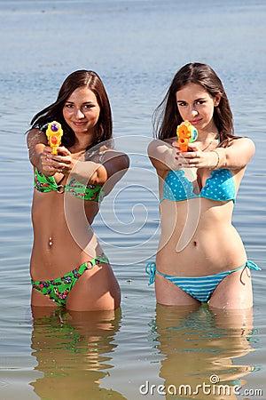 Mädchen in Bikinis mit Gewehren