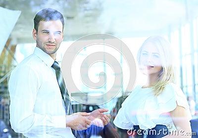 Zwei nette lächelnde junge Wirtschaftler, die im Büro sprechen