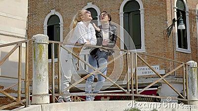 Zwei nette Stadtbewohnerinnen plaudern Stellung auf Damm des italienischen sonnigen Tages der Stadt im Frühjahr stock footage
