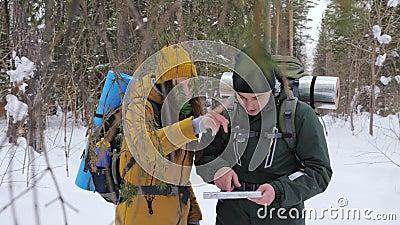 Zwei Touristen mit Rucksäcken, ein junger Mann und ein Mädchen, in einem schneebedeckten Blick des Winters Waldauf eine Papierkar stock video