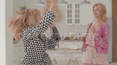 Zwei wunderschöne blonde Kaukasische Frauen tanzen mit einer Flasche Wein und zwei Gläser in der Küche Mädchen in Schlafanzügen stock video