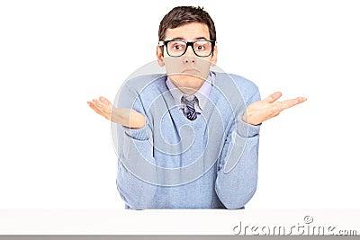 Zweifelhafter Mann, der mit den Händen sitzt und gestikuliert