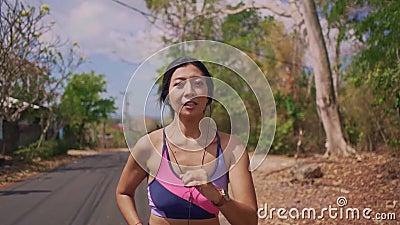 Zwolnione tempo ciągnie z powrotem gimbal strzał młody egzota napad i piękny Azjatycki Indonezyjski kobieta bieg na śladu drogowy zbiory