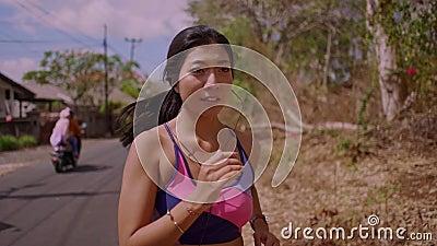 Zwolnione tempo ciągnie z powrotem gimbal strzał młody egzota napad i piękny Azjatycki Indonezyjski kobieta bieg na śladu drogowy zbiory wideo