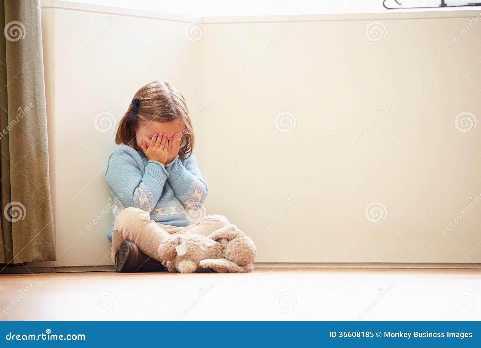 不快乐的幼儿在家坐在角落的地板