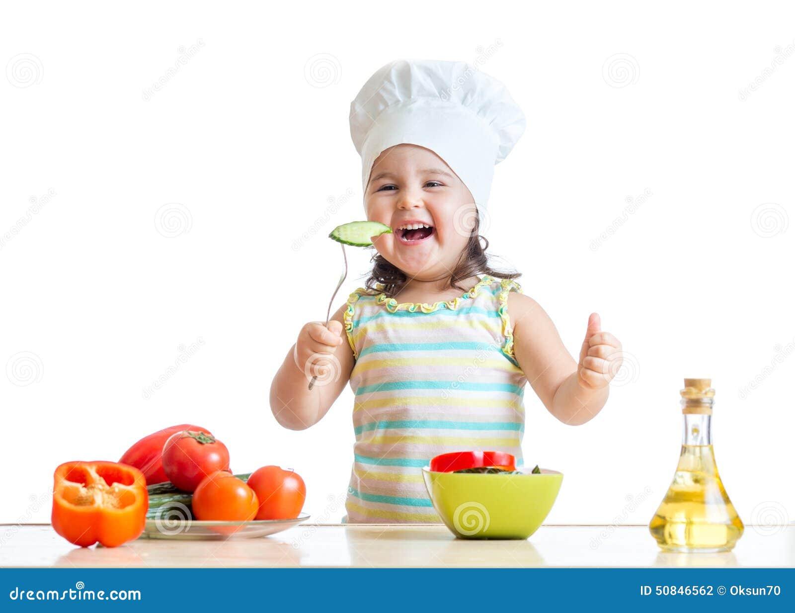 厨师帽子的儿童女孩吃菜的