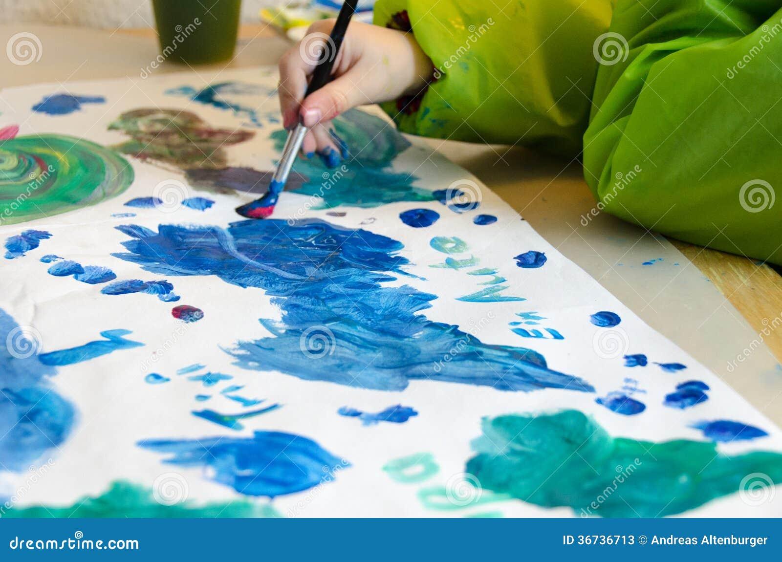 与画笔的儿童绘画和在纸的水彩