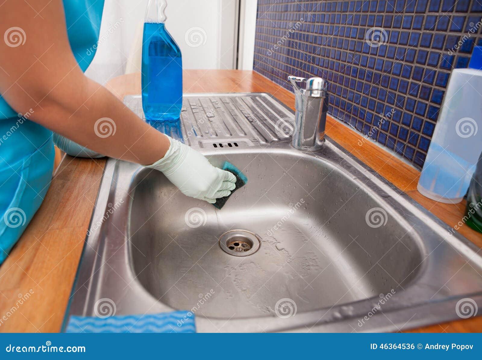 妇女佩带的围裙清洁厨房水槽